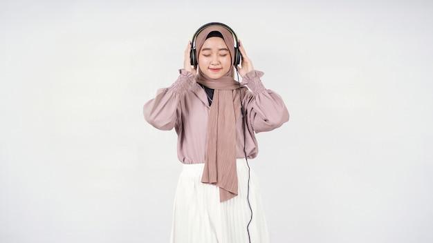 真剣に白い背景で隔離のヒジャーブを聞いているアジアの女性