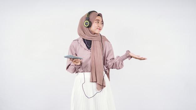 흰색 배경에 격리된 춤을 추면서 음악을 들으며 히잡을 쓴 아시아 여성