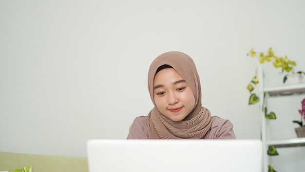 집에서 노트북 화면을 보고 있는 히잡을 쓴 아시아 여성