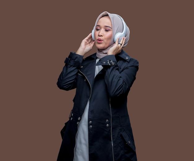 口笛を吹いたり目を閉じたりしながら、ワイヤレスヘッドフォンを着用してポーズをとるヒジャーブのアジアの女性