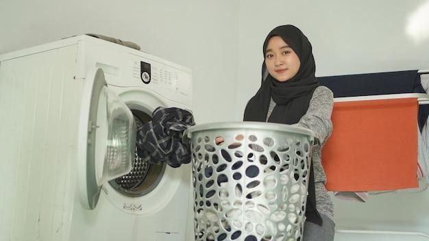 ヒジャーブのアジアの女性は自宅の洗濯機に汚れた服を置きます