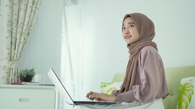 히잡을 쓴 아시아 여성이 노트북을 올려다보며 무언가를 하고 있다
