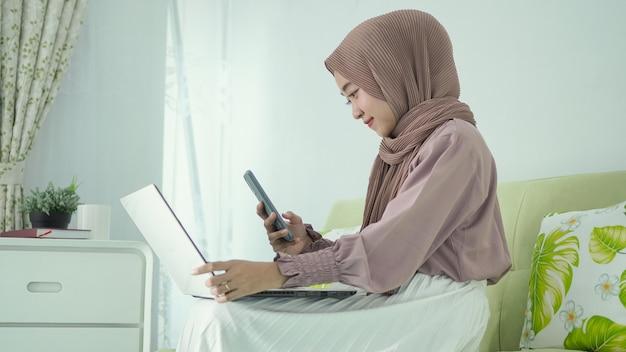 自宅のノートパソコンの画面で写真を撮るヒジャーブのアジアの女性