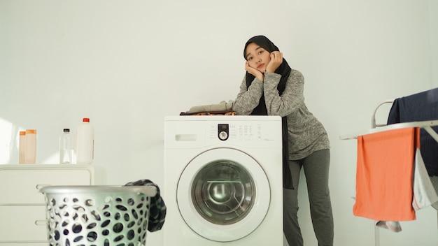 Азиатская женщина в хиджабе ждет, пока стиральная машина начнет вращаться дома