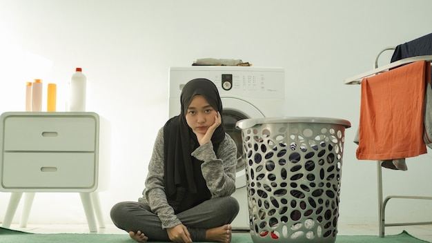 히잡을 쓴 아시아 여성은 집에서 옷을 빨 것이다