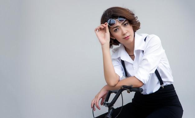 白い背景の彼女の眼鏡を保持している自転車に投稿する流行に敏感なカジュアルなドレスのアジアの女性。