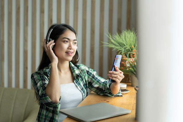 ジーンズと格子縞のシャツのアジアの女性。ソファに座ってオンラインで仕事や勉強をしている若い幸せな女性の肖像画