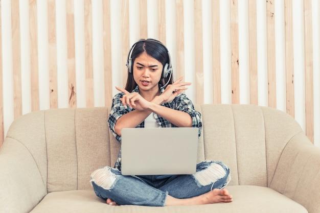청바지와 격자 무늬 셔츠에 아시아 여자입니다. 소파에 앉아 온라인으로 일하거나 공부하는 행복한 젊은 여성의 초상화