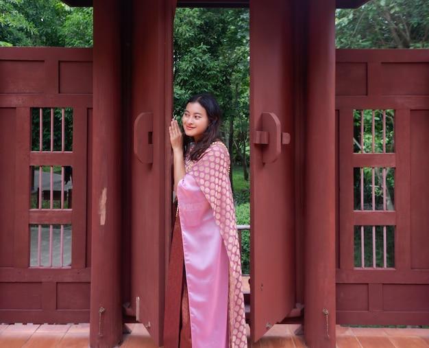 Азиатская женщина в розовом традиционном платье тайского сабая смотрит на кого-то из приоткрытой деревянной двери в старинном стиле