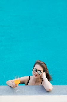 Азиатская женщина в бассейне с бокалом апельсинового сока