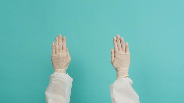 Ppeスーツと医療用手袋のアジアの女性は、青と緑またはティファニーブルーの背景に指を上に向けています。