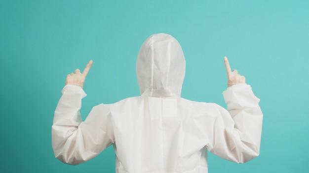 Ppe 정장을 입은 아시아 여성은 얼굴 마스크를 착용하고 의료 장갑은 민트 배경에 손가락을 가리키고 있습니다