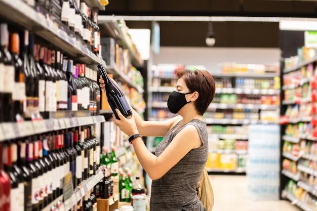 와인 가게에서 와인을 선택하는 보호 마스크를 쓴 아시아 여성