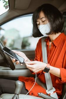 도 차를 운전하는 보호 마스크에 아시아 여자. 그녀의 전화를 충전