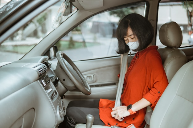 道路で車を運転する保護マスクのアジアの女性。安全な移動とシートベルトの着用