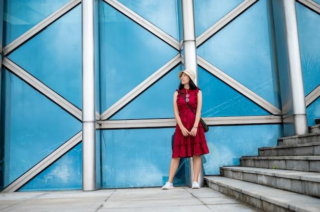 Азиатская женщина в красном платье в современном здании, девушка с городской городской жизнью