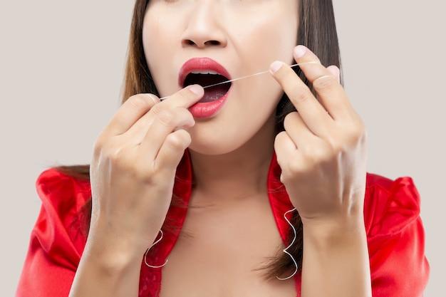 ピンクのデンタルフロスで歯を掃除する赤い絹のローブのアジアの女性