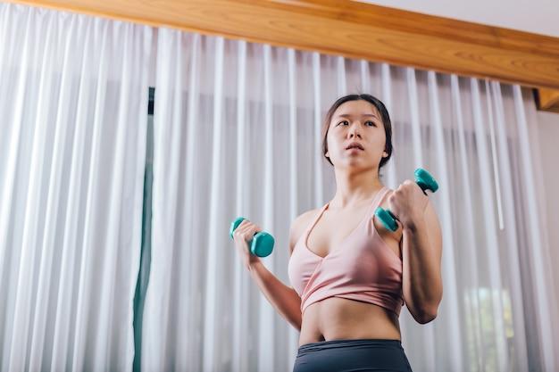 ダンベルを持ち上げるスポーツのブラでアジアの女性