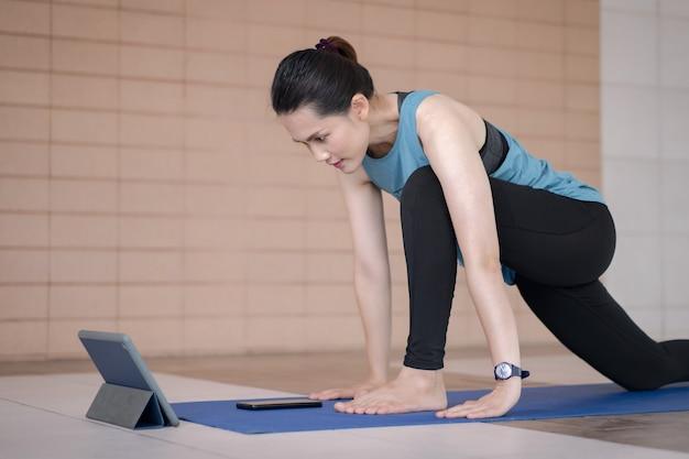スポーツ衣装のアジアの女性は、自宅でデジタルタブレットを介してオンライントレーニングプログラムに続いてトレーニング