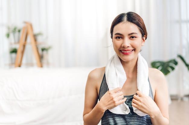 自宅でヨガをした後、肩にタオルを持って座っているスポーツウェアのアジアの女性