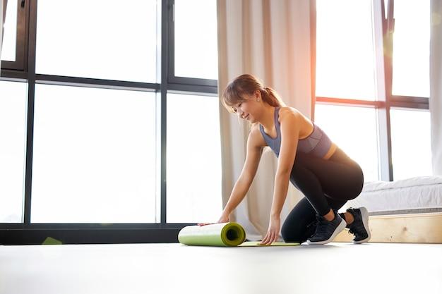 スポーツウェアのアジア人女性は、明るい部屋で、運動前の朝に床にヨガマットを広げます。健康的なライフスタイルとボディケアの概念