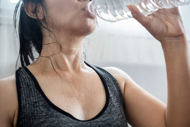 운동복을 입은 아시아 여성은 운동을 하고 땀을 흘리고 운동으로 지친 후 병에서 신선한 물을 마신다