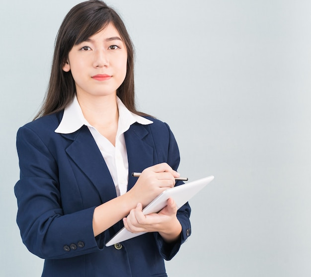 Азиатская женщина в костюме с помощью цифрового планшета компьютера, изолированные на сером фоне