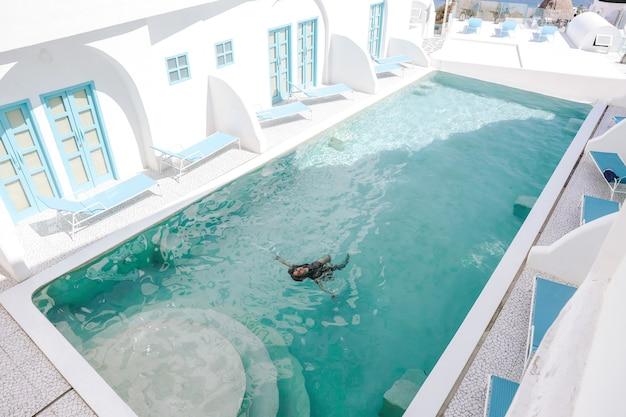 선글라스를 끼고 수영장에서 수영을 하며 여름 휴가를 즐기는 아시아 여성
