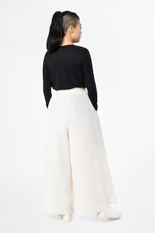 Азиатская женщина в белых брюках палаццо с дизайнерским пространством, повседневная одежда, вид сзади моды