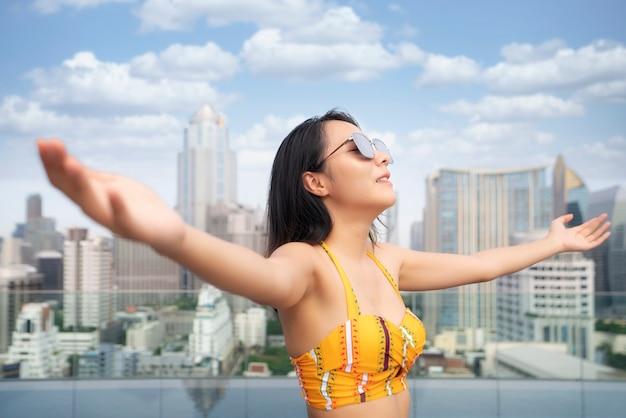 Азиатская женщина в желтом купальнике расслабляется в бассейне на крыше с городом бангкок