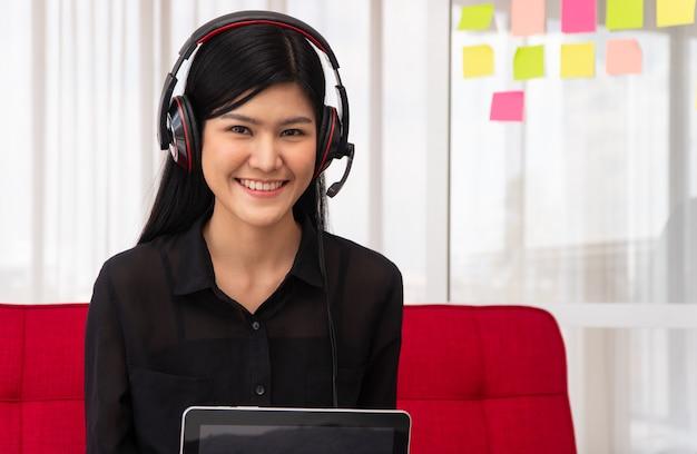 집에서 소파에 앉아 비디오를 녹화하는 아시아 여성 영향력