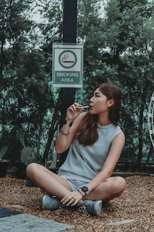 Asian woman inhaling and cigarette vaping female secretly smoking concept of quit smoking