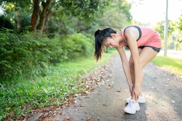 アジアの女性が公園を走っているときに足と膝を負傷した。