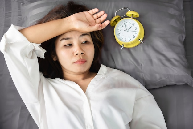 Asian woman insomnia overthinking in bed with alarm clock