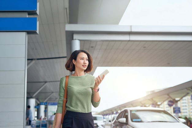 Asian woman is checking her smartphone as she waits in airport in asia.