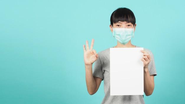 アジアの女性は空白のa4紙を持っており、青と緑またはミントの背景にフェイスマスクまたは医療用マスクを着用してokハンドサインを行います。