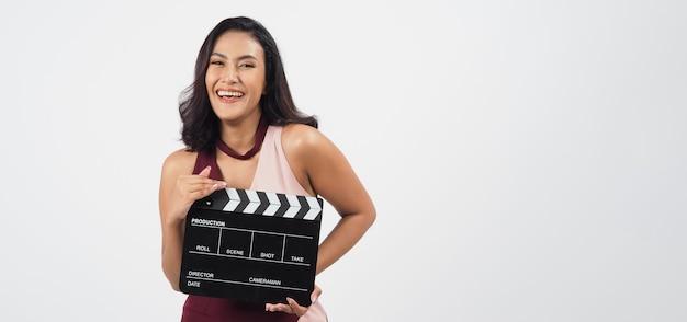 아시아 여성은 흰색 배경에서 비디오 제작, 영화, 영화, 영화 산업에서 클래퍼 보드나 영화 슬레이트를 사용하고 있습니다.