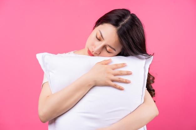 アジアの女性はピンクの枕を抱いています
