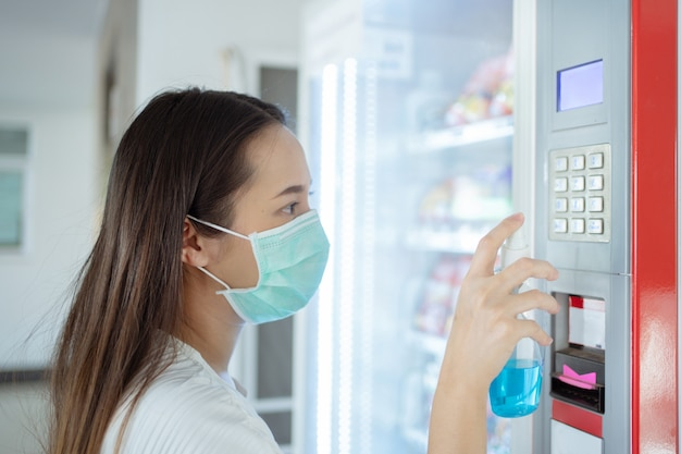 Asian woman is injecting alcohol to kill germs on the button of beverage vending machines