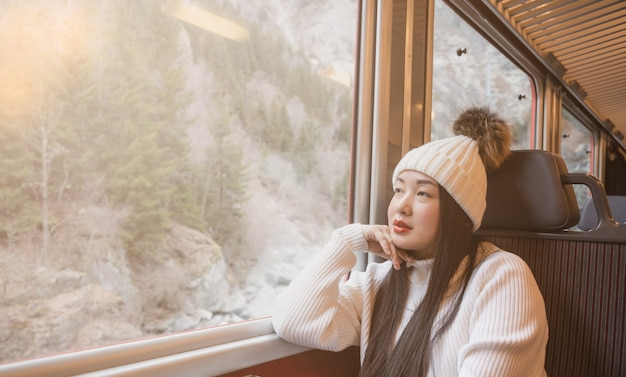 Asian woman is  looking view natural from the window on the train