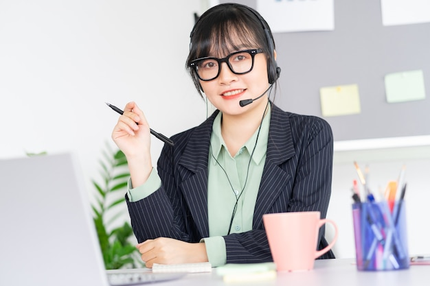Asian woman is meeting online with colleagues via video call app on laptop