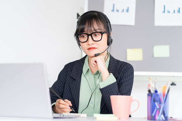 アジアの女性がラップトップのビデオ通話アプリを介して同僚とオンラインで会っています