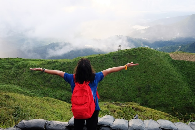 Asian woman is open hands for destination and paradise of golden sunrise and sunset shining to the mist and fog in the jungle on the valley mountain. aerial view the tropical rainforest in thailand.