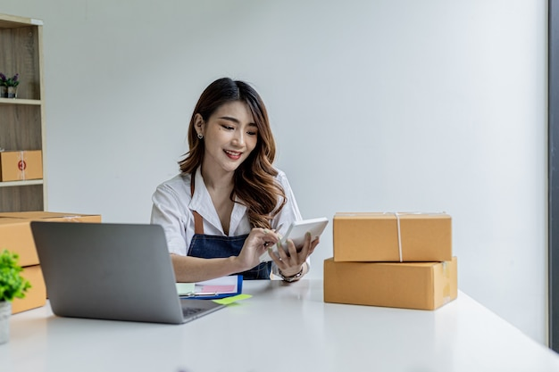 An asian woman is pressing a white calculator, she owns an online store, she is using an order amount calculator to get a summary of the amount customers have to pay. online selling concept.
