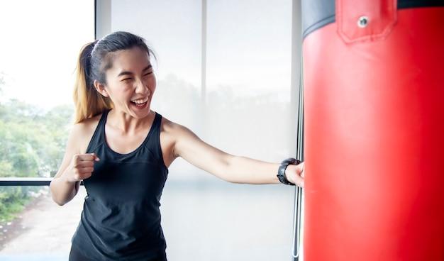 아시아 여성이 체육관에서 재미로 샌드백을 펀칭하고 있습니다.