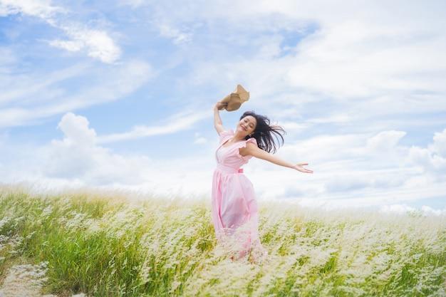 アジアの女性は牧草地でさわやかです。彼女はジャンプします。