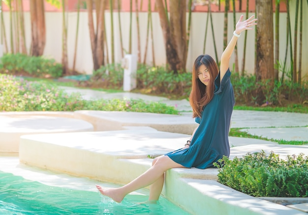 アジアの女性は、夏のリゾートガーデンとスイミングプールでリラックスしています