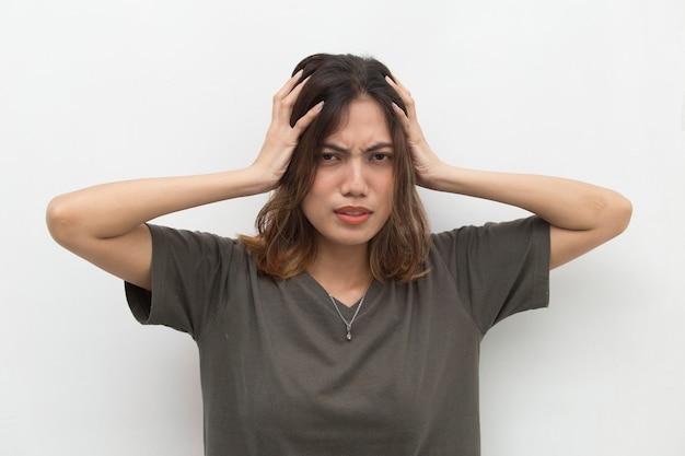 アジアの女性が背景に頭痛を立てている