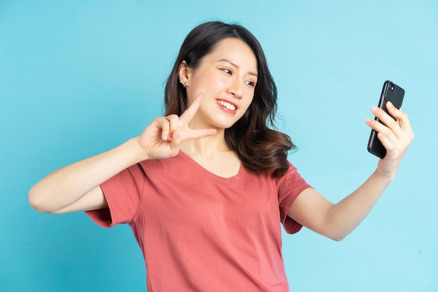 아시아 여자는 스마트 폰을 사용하여 셀카 찍기