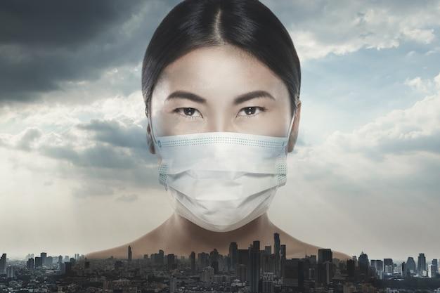 都市でのウイルスの流行中に、アジアの女性が顔のマスクを着用している